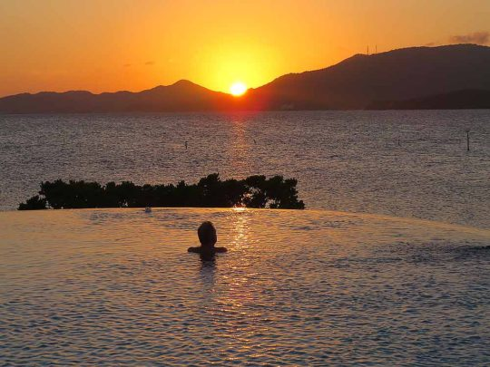 guest in the infinity pool watching the sunset